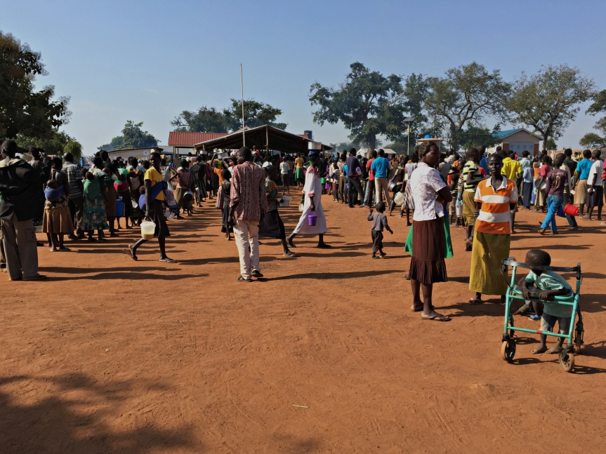 En el centro de recepción de Nyumazi los refugiados recién llegados esperan su turno para recibir comidas.jpg